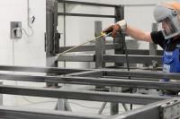 Mann benetzt eine Fläche mit dem FT 200 Reiniger